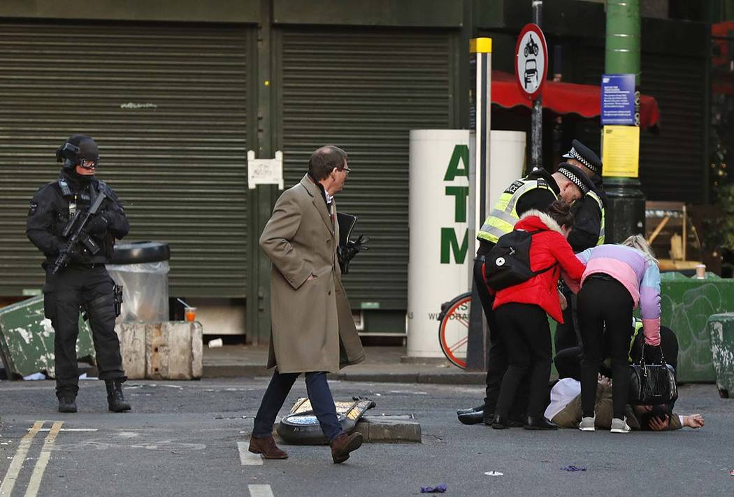 A person is assisted after falling when Police evacuated people from Borough Market on the sout ...