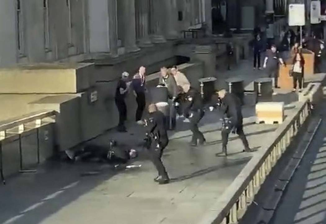 In this grab taken from video made available by @HLOBlog, a man is surrounded by armed police a ...