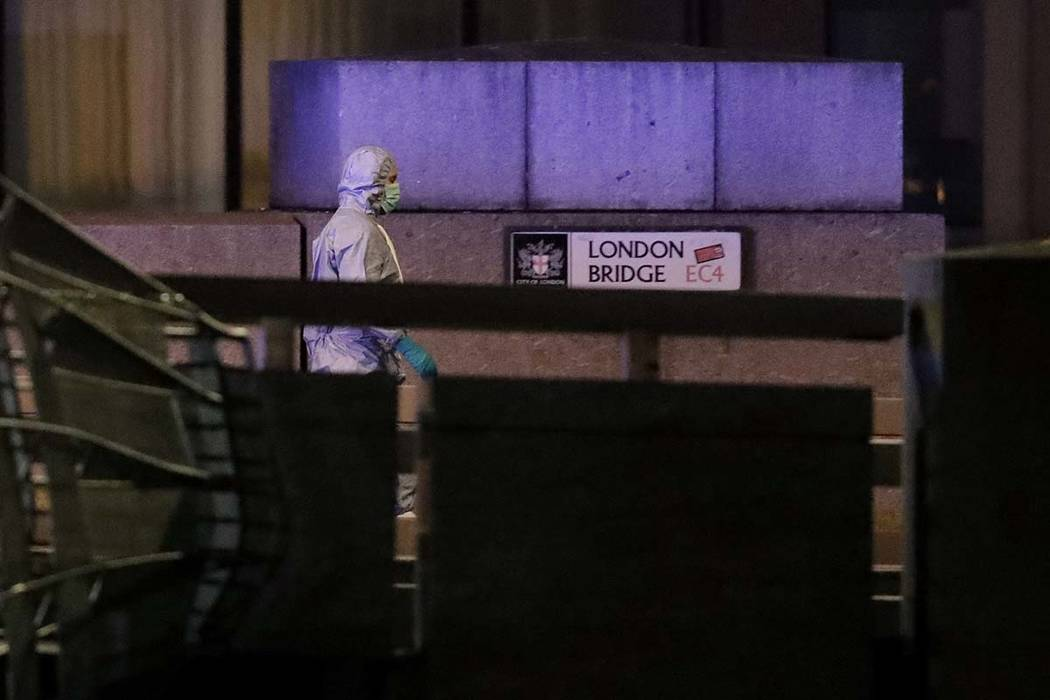 A police forensic officer walks by a sign where a man was shot dead by police on London Bridge ...