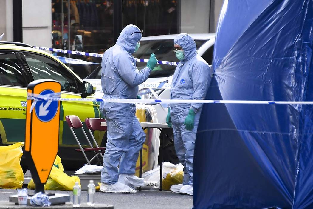 Forensic workers attend the scene on London Bridge in London, Saturday, Nov. 30, 2019. UK count ...