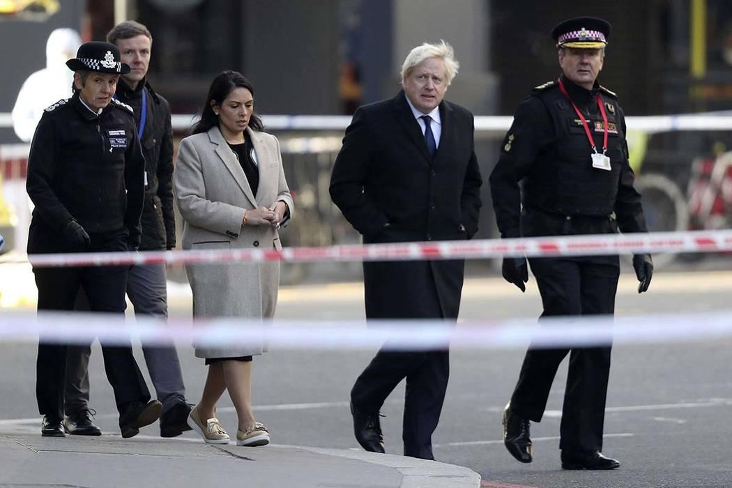 Britain's Prime Minister Boris Johnson, second right, Home Secretary Priti Patel, center, and M ...