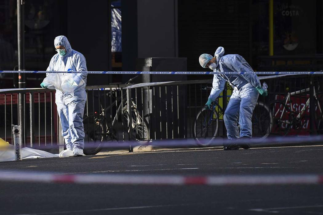 Forensic officers attend the scene in central London, Saturday, Nov. 30, 2019, after an attack ...