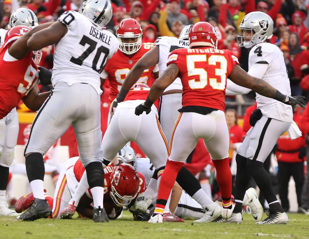 Kansas City Chiefs outside linebacker Justin Houston (50), below, intercepts Oakland Raiders qu ...