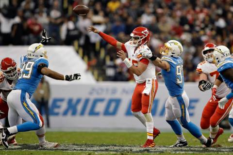 Kansas City Chiefs quarterback Patrick Mahomes throws a pass under pressure from Los Angeles Ch ...