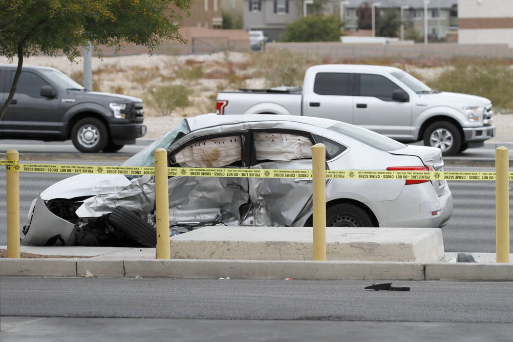 Las Vegas police officers investigate a fatal crash at Durango Drive and Russell Road in southw ...