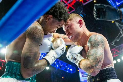 Tyler McCreary, left, takes a hit from Carl Frampton during round 4 of their WBC super featherw ...