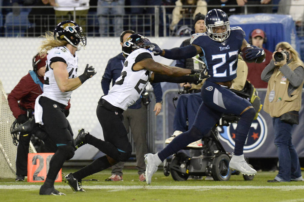 Tennessee Titans running back Derrick Henry (22) runs past Jacksonville Jaguars safety Jarrod W ...