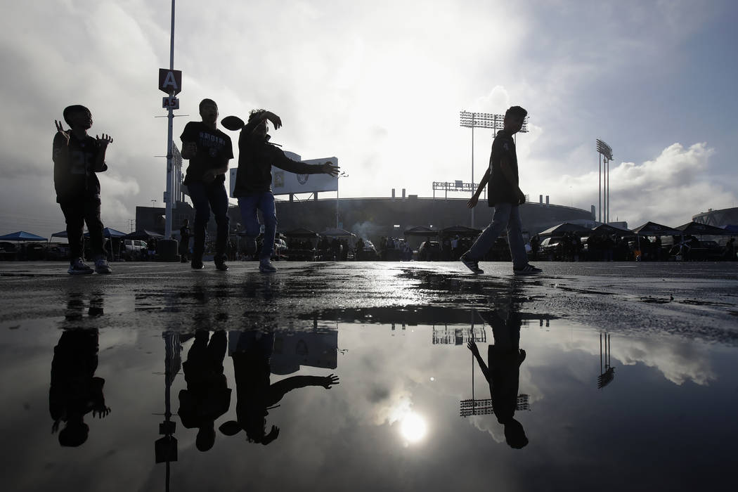 Fans play football while tailgating at RingCentral Coliseum before an NFL football game between ...