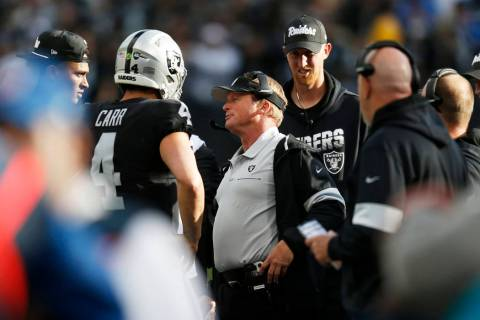 Oakland Raiders head coach Jon Gruden, center, talks with quarterback Derek Carr (4) during the ...