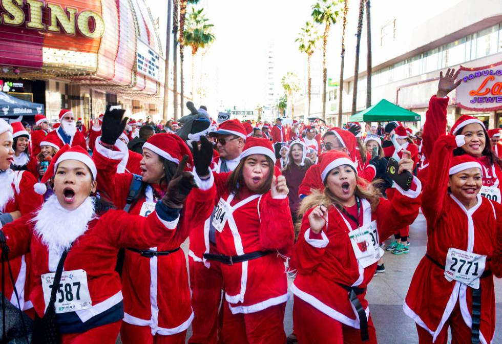 Santas dance during the pre-entertainment on the Third Street Stage at Fremont Street Experienc ...