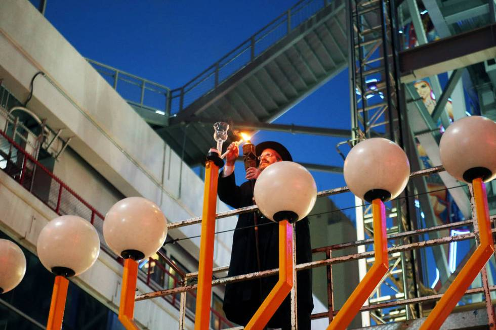 Rabbi Shea Harlig lights the shamesh candle that's used to light the other candles on the Grand ...