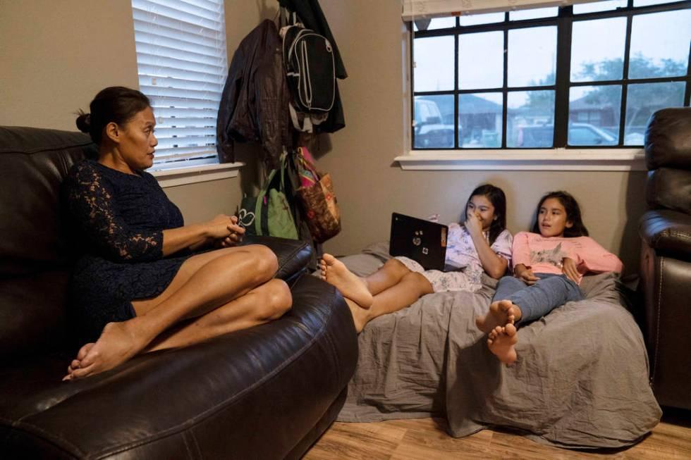 Margarita DeLoach, 45, talks to her daughters Maura Castro, 10, center, and Mililani Castro, 12 ...