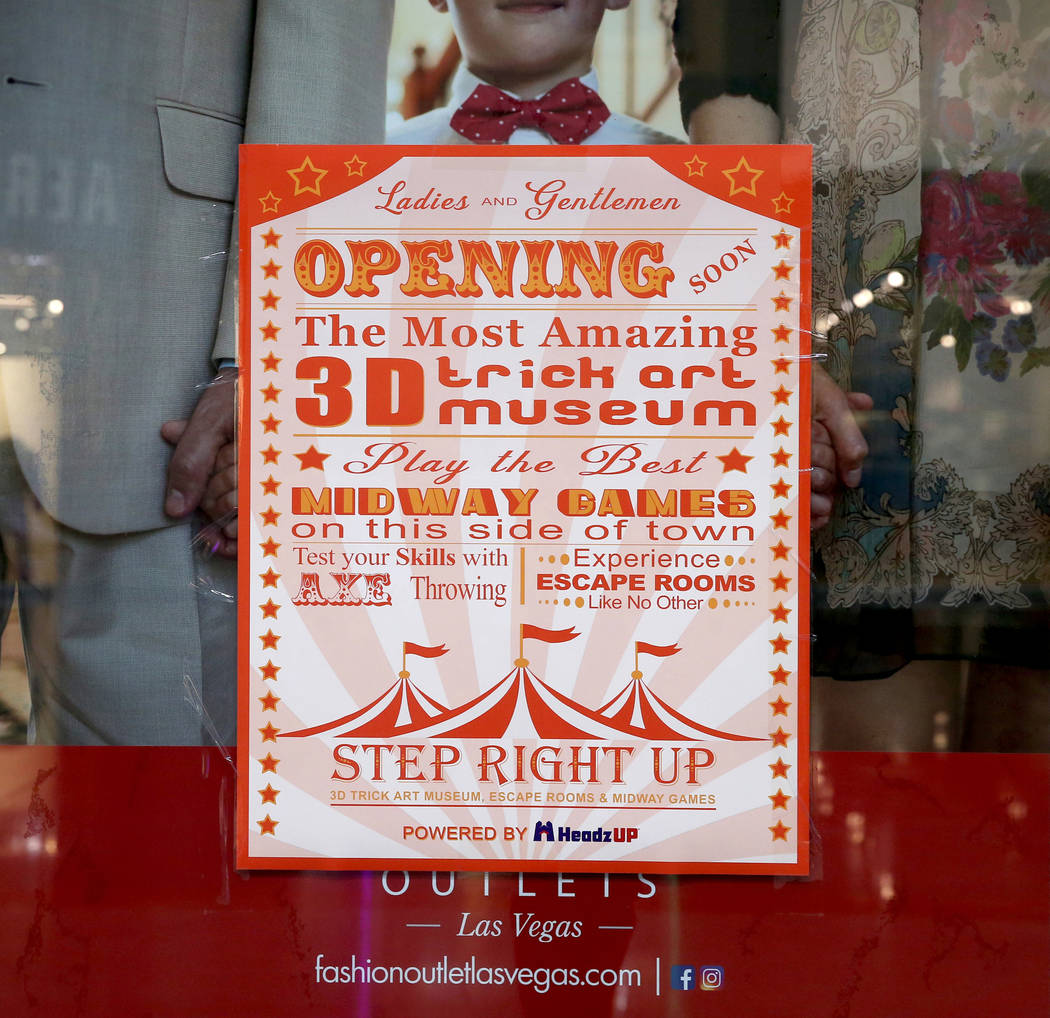 A poster of a new attraction, Step Right Up, is pasted over an advertisement at Fashion Outlets ...