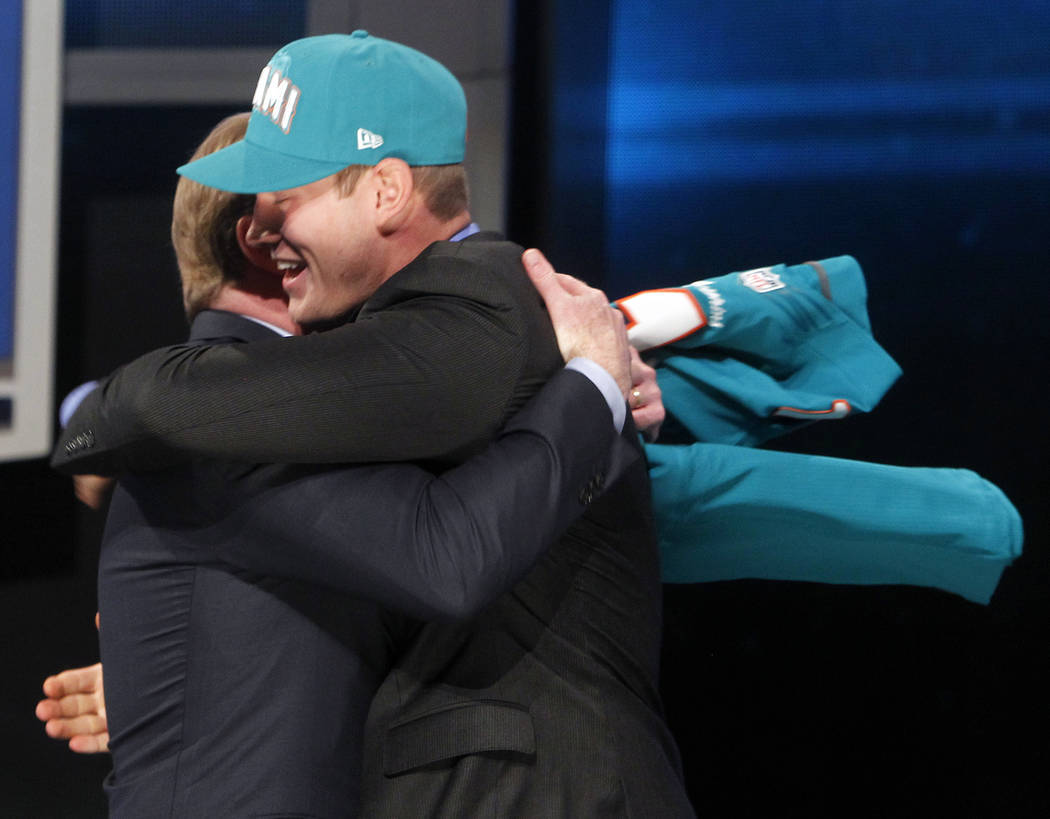 Texas A&M quarterback Ryan Tannehill, right, hugs NFL Commissioner Roger Goodell after bein ...