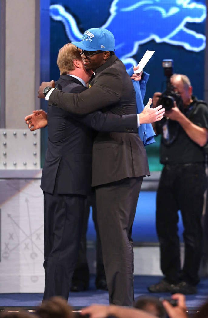 Ezekiel Ansah, from Brigham Young, hugs NFL Commissioner Roger Goodell after being selected fif ...