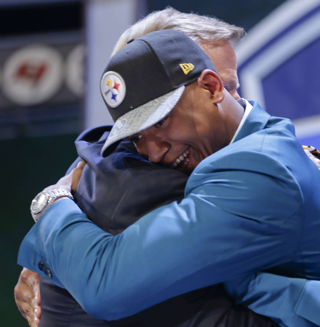 Ohio State outside linebacker Ryan Shazier hugs NFL commissioner Roger Goodell after being sele ...