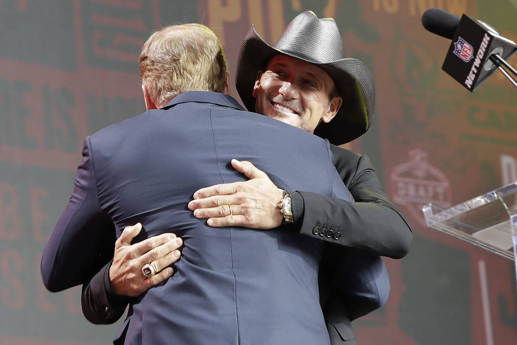 Country music star Tim McGraw hugs NFL Commissioner Roger Goodell ahead of the second round of ...