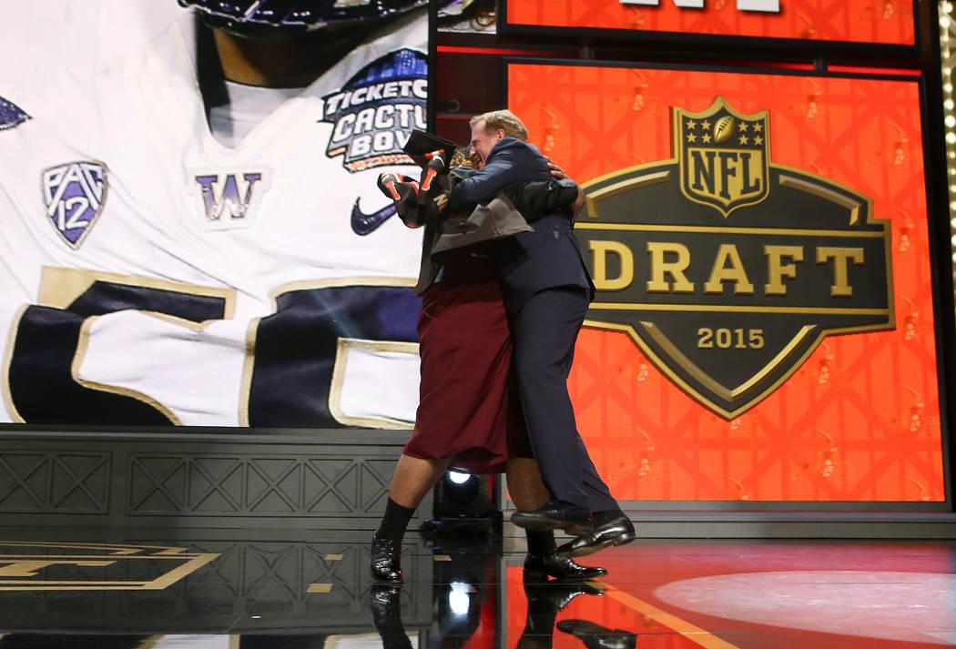 Washington defensive lineman Danny Shelton hugs NFL Commissioner Roger Goodell on stage after ...