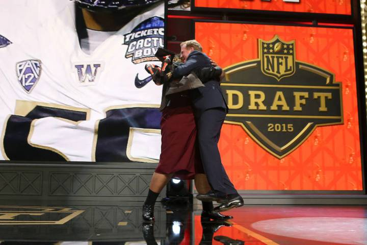 Washington defensive lineman Danny Shelton hugs NFL Commissioner Roger Goodell on stage after ...