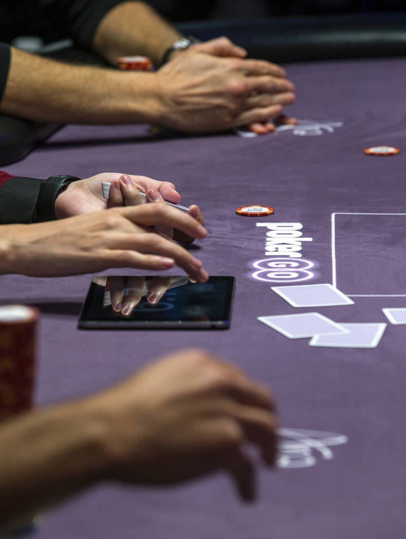 A dealer, center, keeps the playing time on a side table during the Poker Masters 2019 broadcas ...