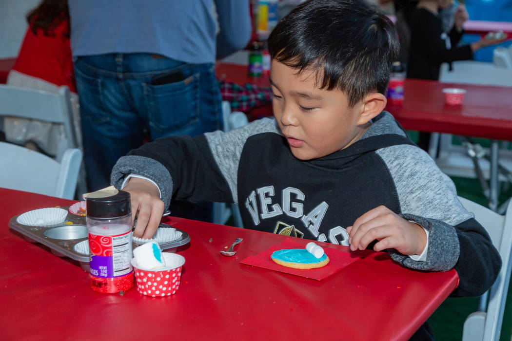 A participant of Holiday Express at Springs Preserve decorates a cookie. (Springs Preserve)