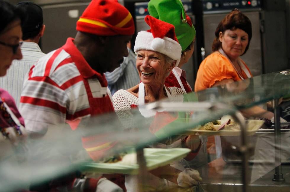 Volunteers Barbara Pickett, middle, and Henry Brown interact while preparing holiday meals duri ...