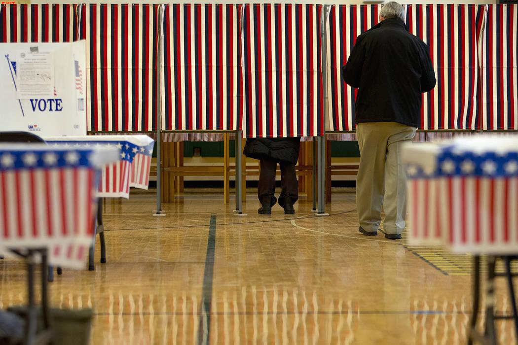 People cast their votes in the presidential primary at Windham High School in Windham, N.H., Tu ...