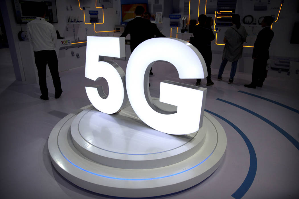 Visitors stand near a 5G logo at a display the PT Expo in Beijing in 2018. (AP Photo/Mark Schie ...