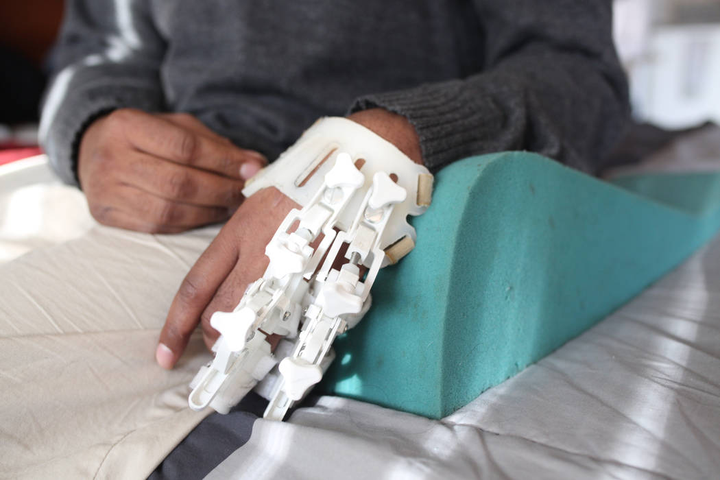 Jeffrey Fikes relaxes on his bed with his splint and foam rest, in his supportive housing unit ...