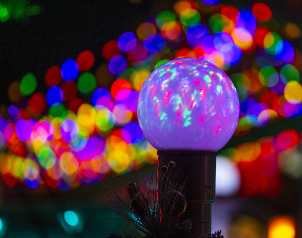 An illuminated globe as part of the holiday lights display in the yard of Maria Acosta and Juan ...