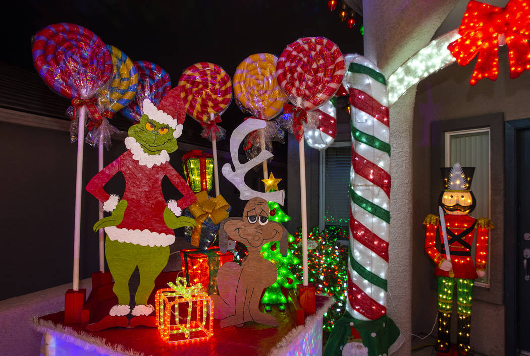 The Grinch Who Stole Christmas is part of the holiday lights display in the yard of Maria Acost ...