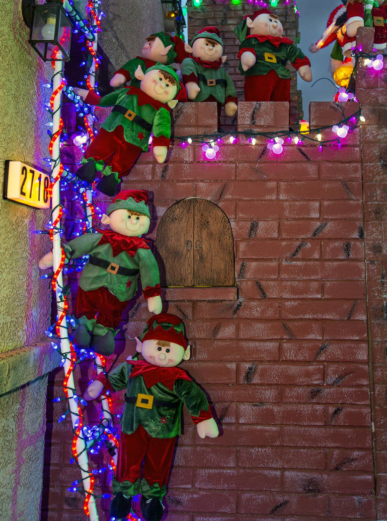 A group of elves on a ladder as part of the holiday lights display in the yard of Maria Acosta ...