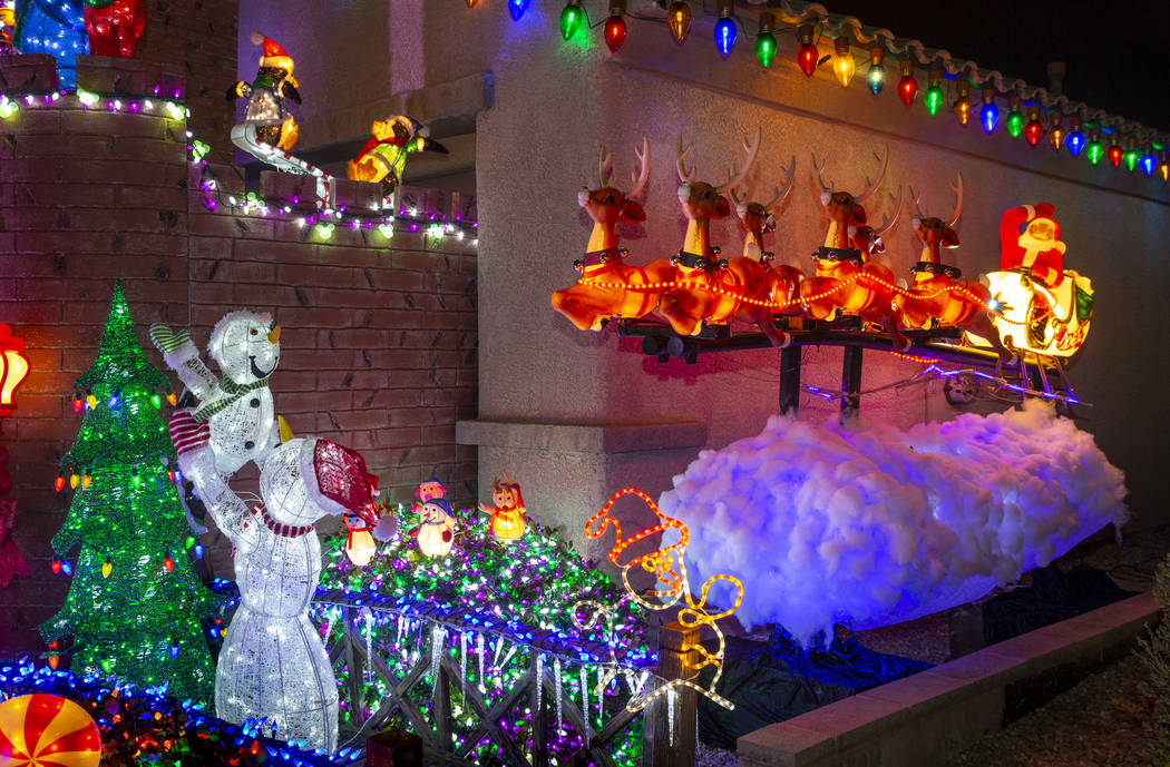 Santa on his sleigh as part of the holiday lights display in the yard of Maria Acosta and Juan ...