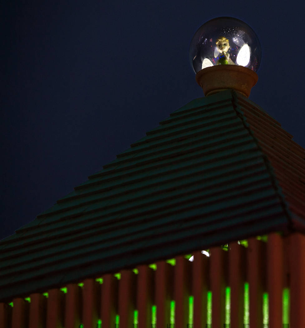 Tinkerbell sits atop a clock tower as part of the holiday lights display in the yard of Maria A ...