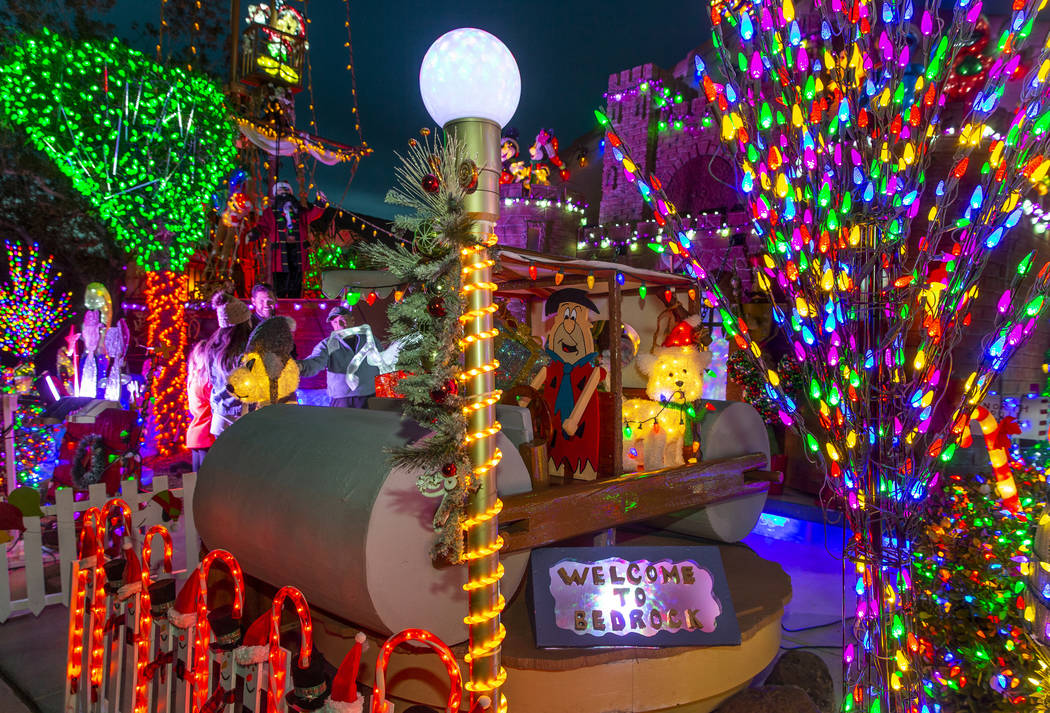 Fred Flintstone in his car is apart of the holiday lights display in the yard of Maria Acosta a ...