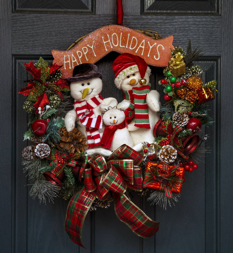 The wreath on the front door is the first item ever hung for the holiday lights display in the ...