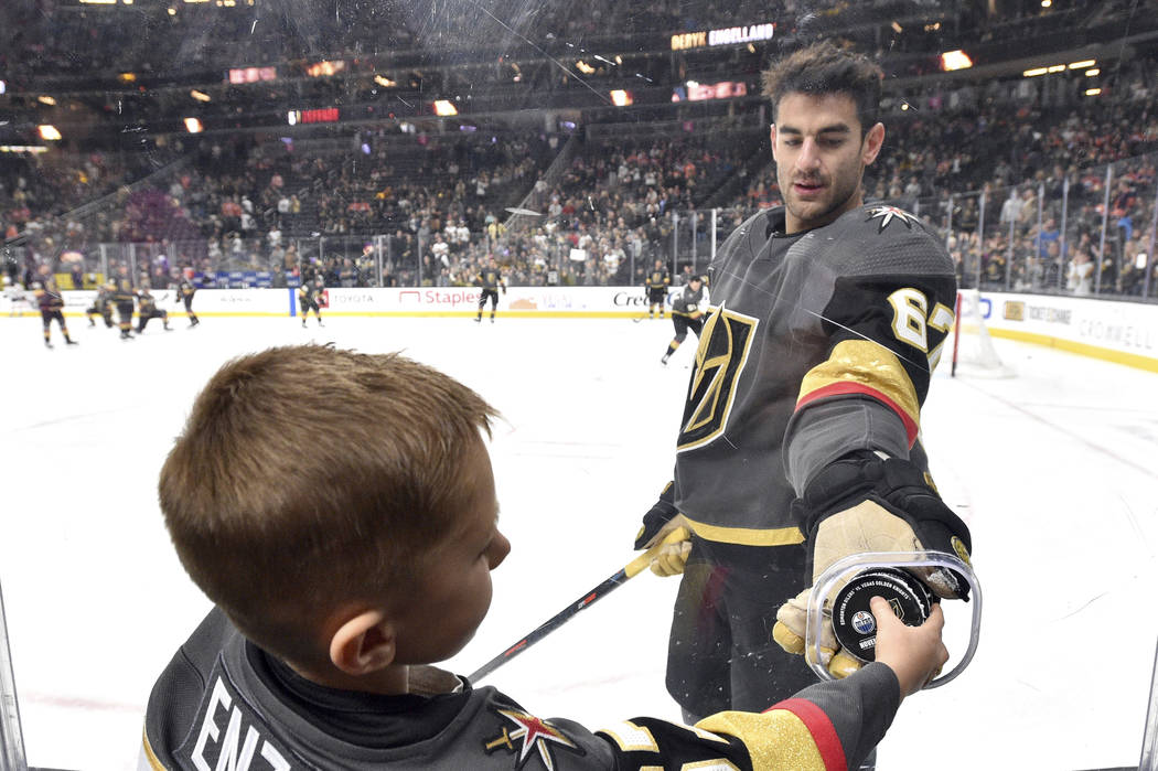 Vegas Golden Knights left wing Max Pacioretty hands a puck though a photographer's hole to a yo ...