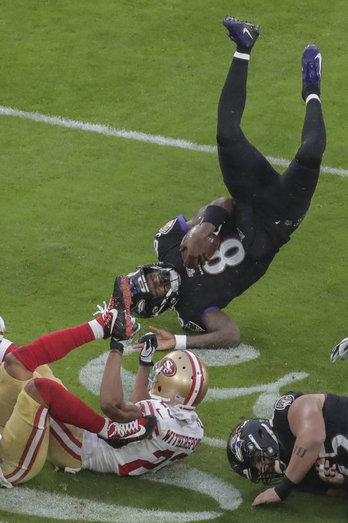 Baltimore Ravens quarterback Lamar Jackson (8) flips over after being tripped by San Francisco ...