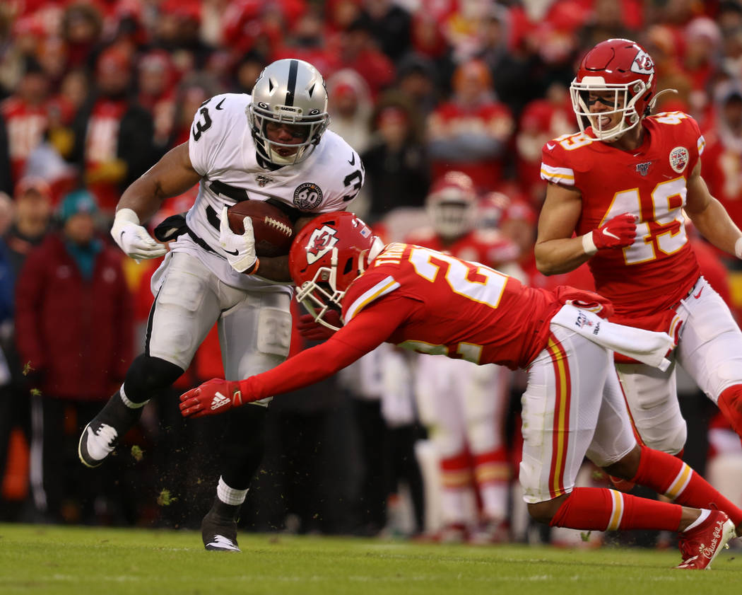 Oakland Raiders running back DeAndre Washington (33) is tackled by Kansas City Chiefs free safe ...