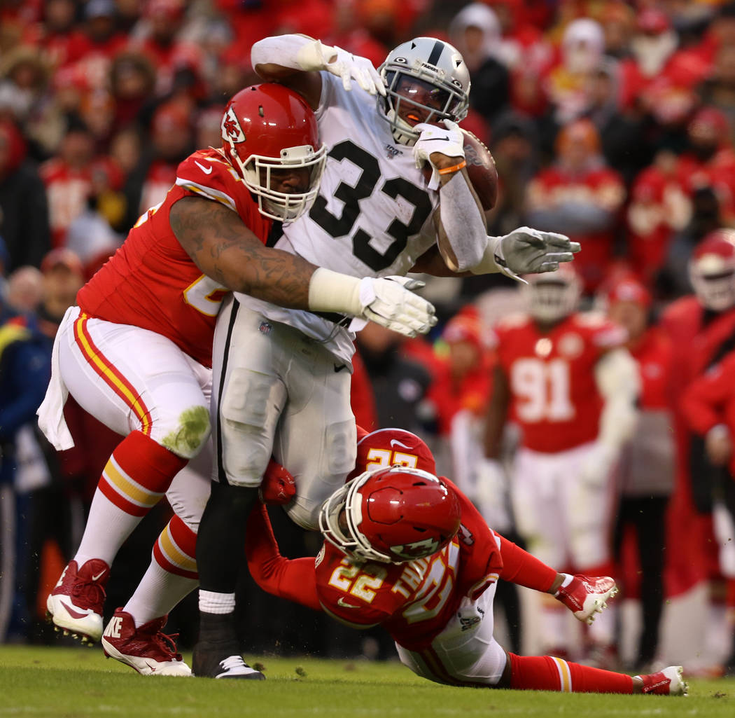 Oakland Raiders running back DeAndre Washington (33) fights for yards as Kansas City Chiefs fre ...