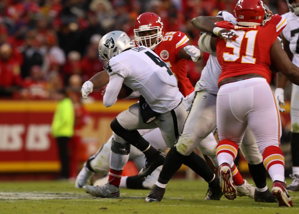 Oakland Raiders quarterback Derek Carr (4) scrambles with the football as Kansas City Chiefs de ...