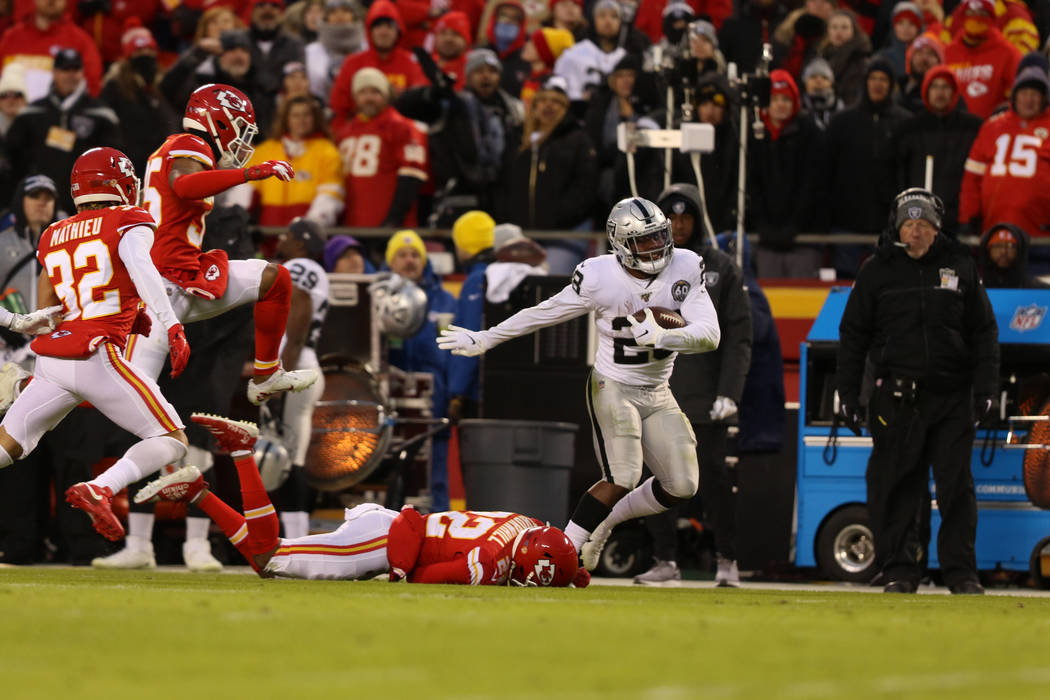 Oakland Raiders running back Josh Jacobs (28) fights for yards as Kansas City Chiefs free safet ...