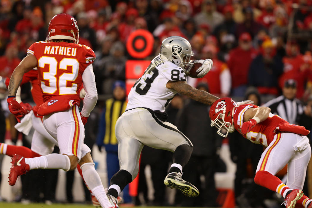 Oakland Raiders tight end Darren Waller (83) stiff arms Kansas City Chiefs cornerback Kendall F ...