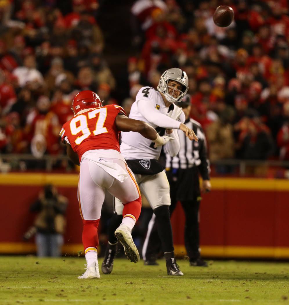 Oakland Raiders quarterback Derek Carr (4) throws the football as he is pressured by Kansas Cit ...