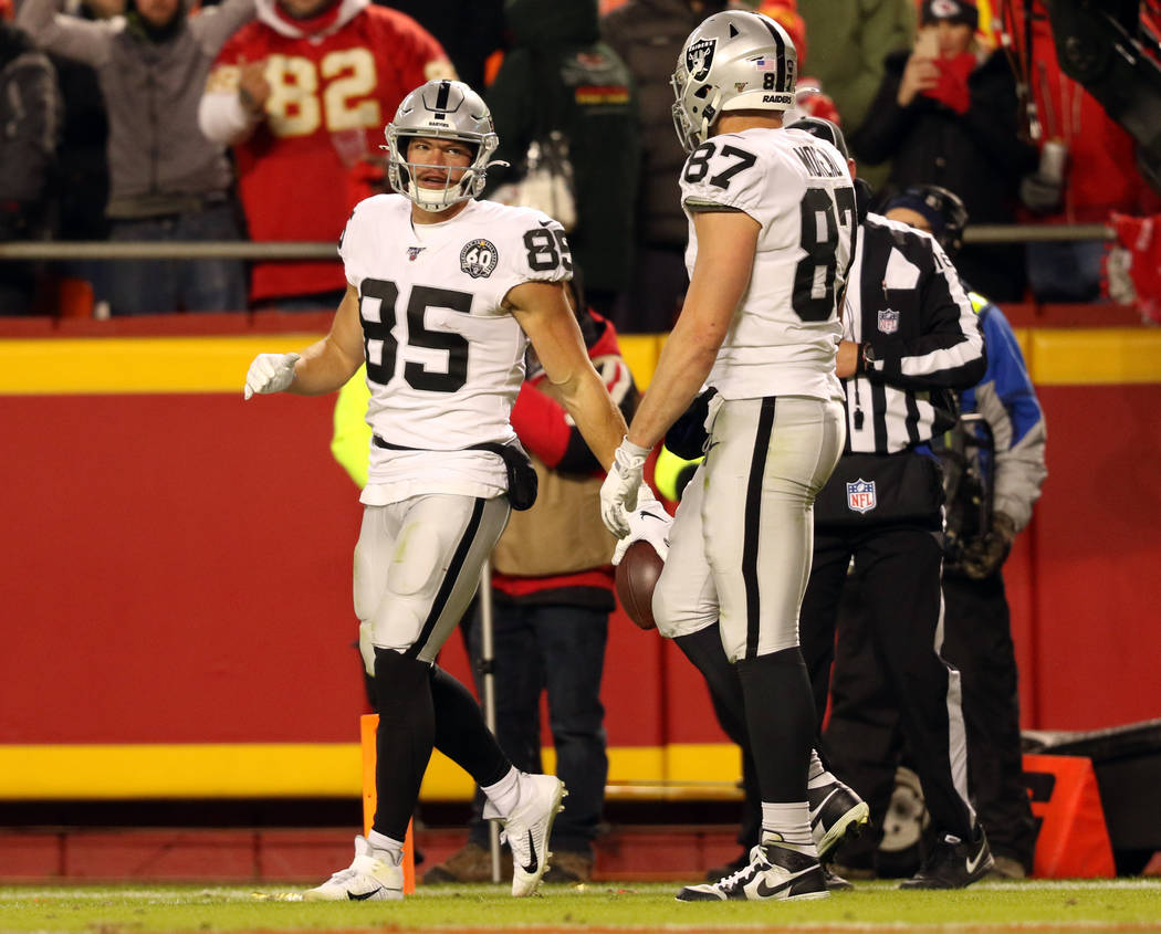Oakland Raiders tight end Derek Carrier (85) holds on to the football as tight end Foster Morea ...