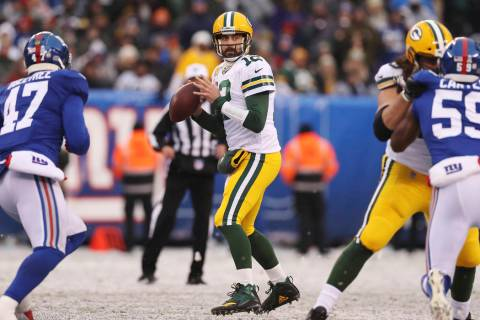 Green Bay Packers quarterback Aaron Rodgers (12) looks to make a pass while New York Giants out ...