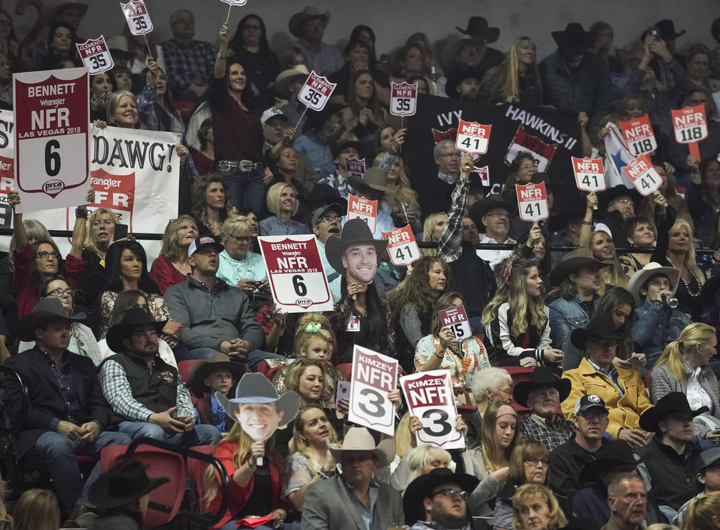 Spectators cheer during the eighth go-round of the National Finals Rodeo at the Thomas & Ma ...