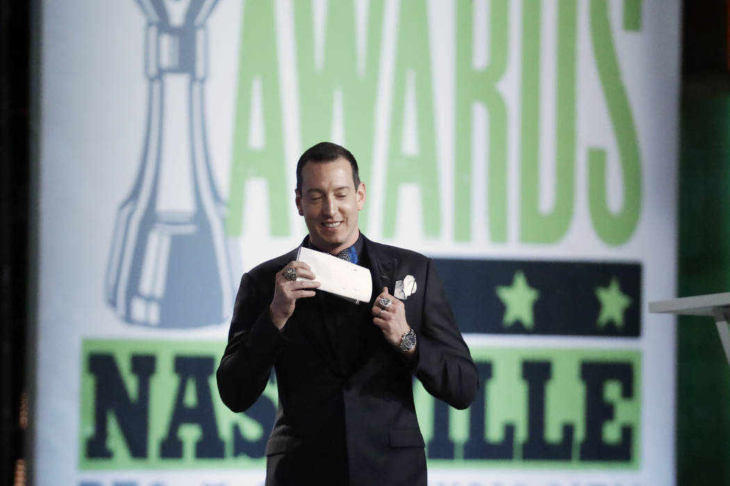 Kyle Busch pulls out his speech as he walks to the podium at the NASCAR Cup Series Awards on Th ...