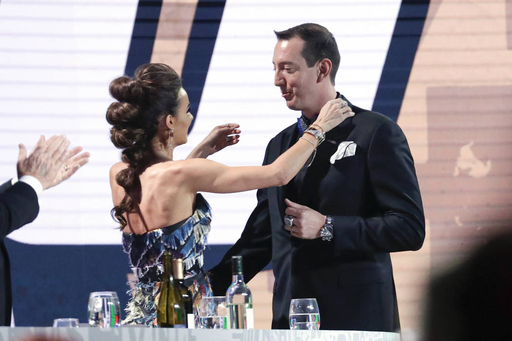 Kyle Busch, right, is hugged by his wife, Samantha, after Busch was honored as the season champ ...