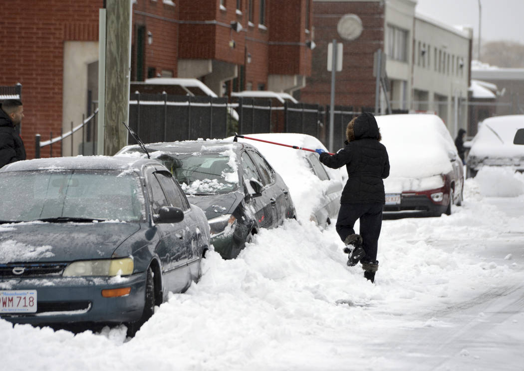 A woman clears snow from a car on Grove Street in Springfield's North End neighborhood followin ...